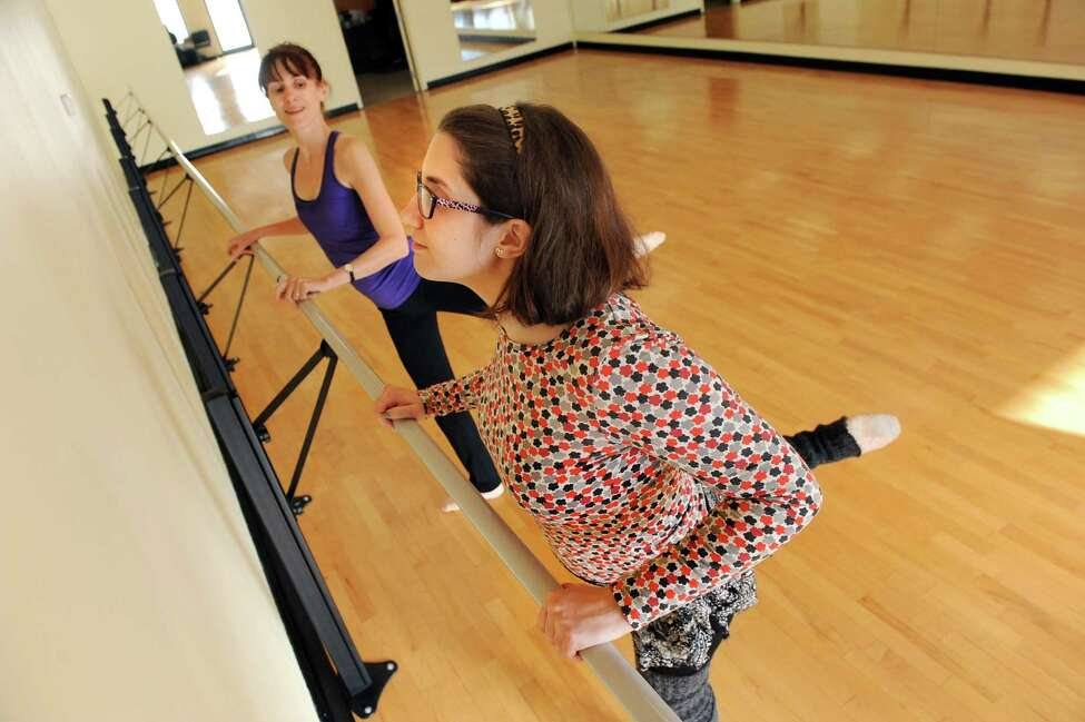 Laura Casellini, 22, of East Greenbush, right, works on the bar during a ballet lesson with Gail Tassarotti on Tuesday, Dec. 30, 2014, at Albany Dance and Fitness in Colonie, N.Y. Casellini suffered a traumatic brain injury after a car accident and dancing is part of her ongoing therapy. (Cindy Schultz / Times Union)