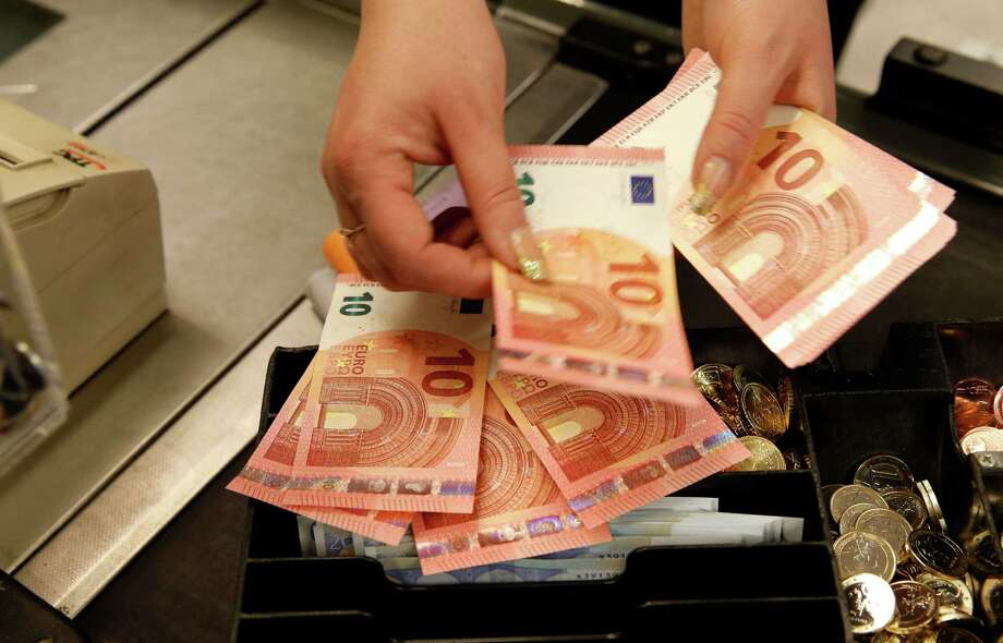 A cashier checks euro bills before opening shop this week in Vilnius, Lithuania. Photo: Mindaugas Kulbis, STR / AP