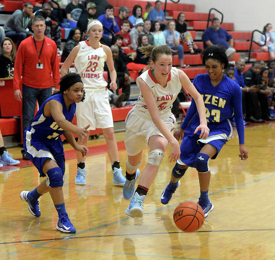 Lumberton's Hannah Holt looks to get past the pressure of Ozen's Rochelle Harmon (#11) (left) and Aubrey Hubert as she closes in toward the basket during Friday night's game at Lumberton High School.  Photo taken Wednesday, December 31, 2014  Kim Brent/The Enterprise Photo: KIM BRENT / Beaumont Enterprise