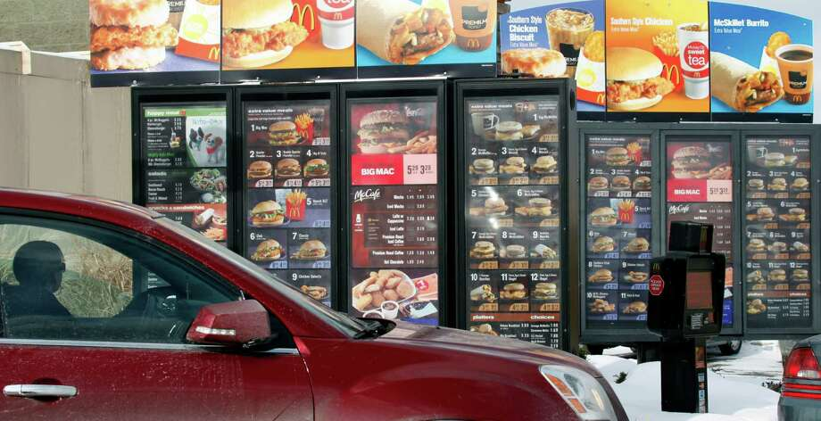 FILE - In this Jan. 26, 2009, file photo, a customer looks at the menu at a McDonald's drive-thru in Williamsville, N.Y. As people express distaste for food they think is overly processed, chains including McDonald's and Taco Bell are trying to shed their reputation for serving reheated meals that are kept intact with chemicals. (AP Photo/David Duprey, File) Photo: David Duprey, STF / AP