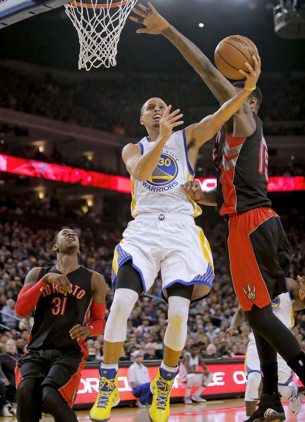 Warriors' Stephen Curry, 30 drives past the Raptors' Amir Johnson, 15 during the first half, as the Golden State Warriors take on the Toronto Raptors in NBA action at Oracle Arena in Oakland, Calif., on Friday Jan. 2, 2015.