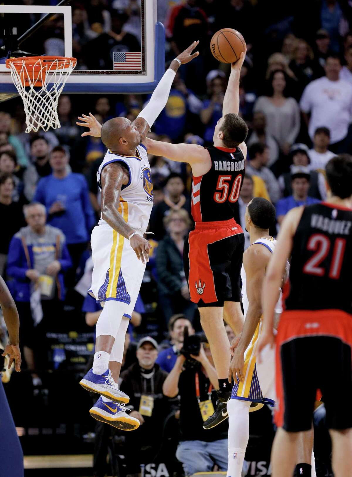 Warriors' Andre Iguodala, 9 defends against the Raptors' Tyler Hansbrough, 50 during the second half, as the Golden State Warriors went on to beat the Toronto Raptors 126-105 in NBA action at Oracle Arena in Oakland, Calif., on Friday Jan. 2, 2015.