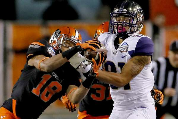 Oklahoma State cornerback Ramon Richards (18) breaks up a pass intended for Washington wide receiver Brayden Lenius during the first half of the Cactus Bowl NCAA college football game, Friday, Jan. 2, 2015, in Tempe, Ariz. (AP Photo/Matt York)