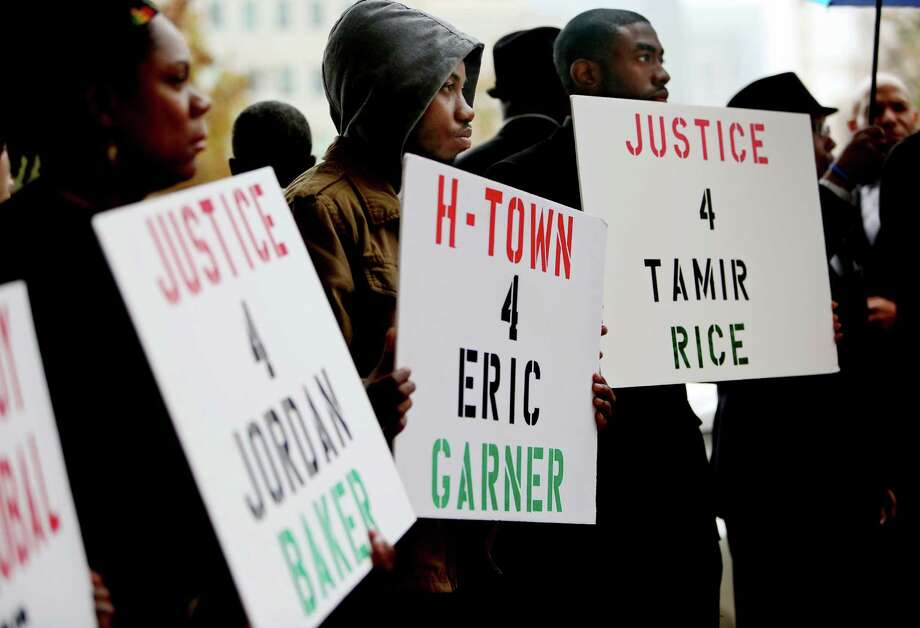 Activists hold signs for Jordan Baker, who was shot on Jan. 16 by an off-duty Houston police officer, Eric Garner, who died in Staten Island on July 17, after a police officer put him in a grappling hold, and 12-year-old Tamir Rice, who was shot by Cleveland police on Nov. 22, outside the Harris County Criminal Justice Center, Tuesday, Dec. 23, 2014, in Houston, before a grand jury declined to indict Houston police officer Juventino Castro in the shooting death of 26-year-old  Baker. Castro shot Baker while off duty but in uniform, working security at a mall. (AP Photo/Houston Chronicle, Gary Coronado) MANDATORY CREDIT Photo: Gary Coronado, MBO / Houston Chronicle
