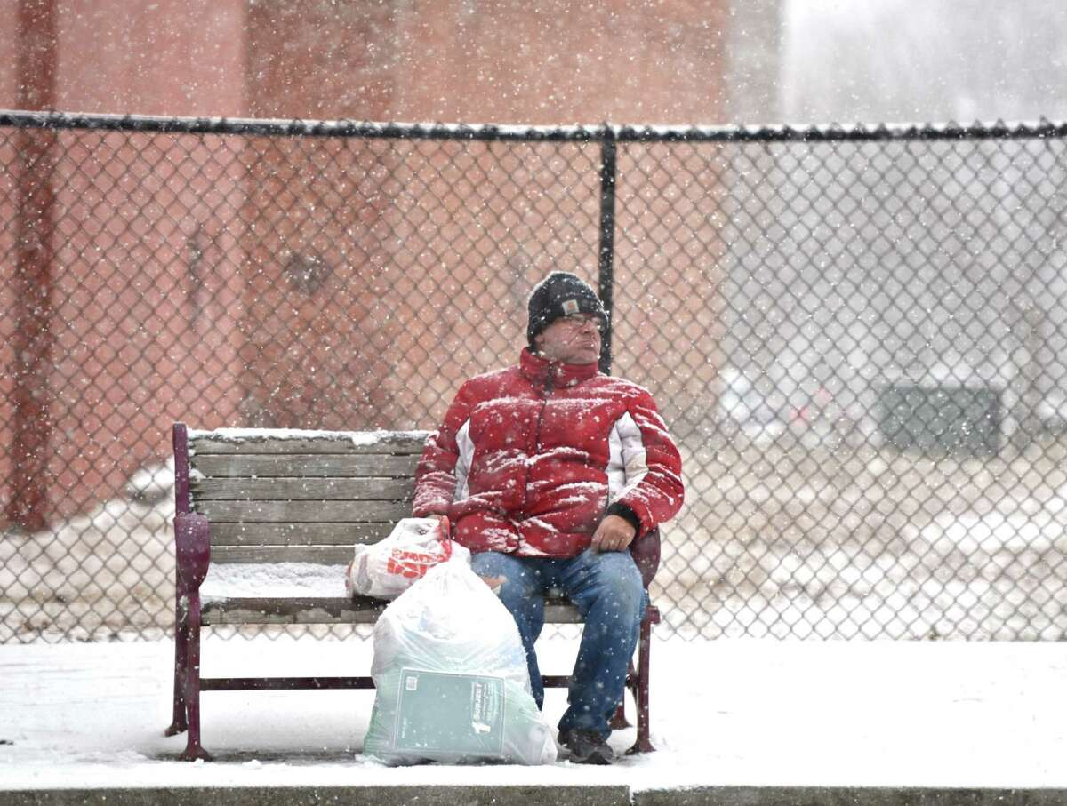 Larry Keeler, 62, of Danbury, waits patiently for his bus, along Main Street, during an afternoon snow storm in Danbury, Conn, on Saturday, January 3, 2015.