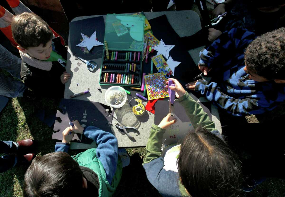 Children gather to decorate stars at a Black Lives Matter story time action near Lake Merritt in Oakland, Calif. on Saturday, Jan 3, 2015. The Colorful Mamas of the 99 Percent organized the event to engage children in current social and political issues.