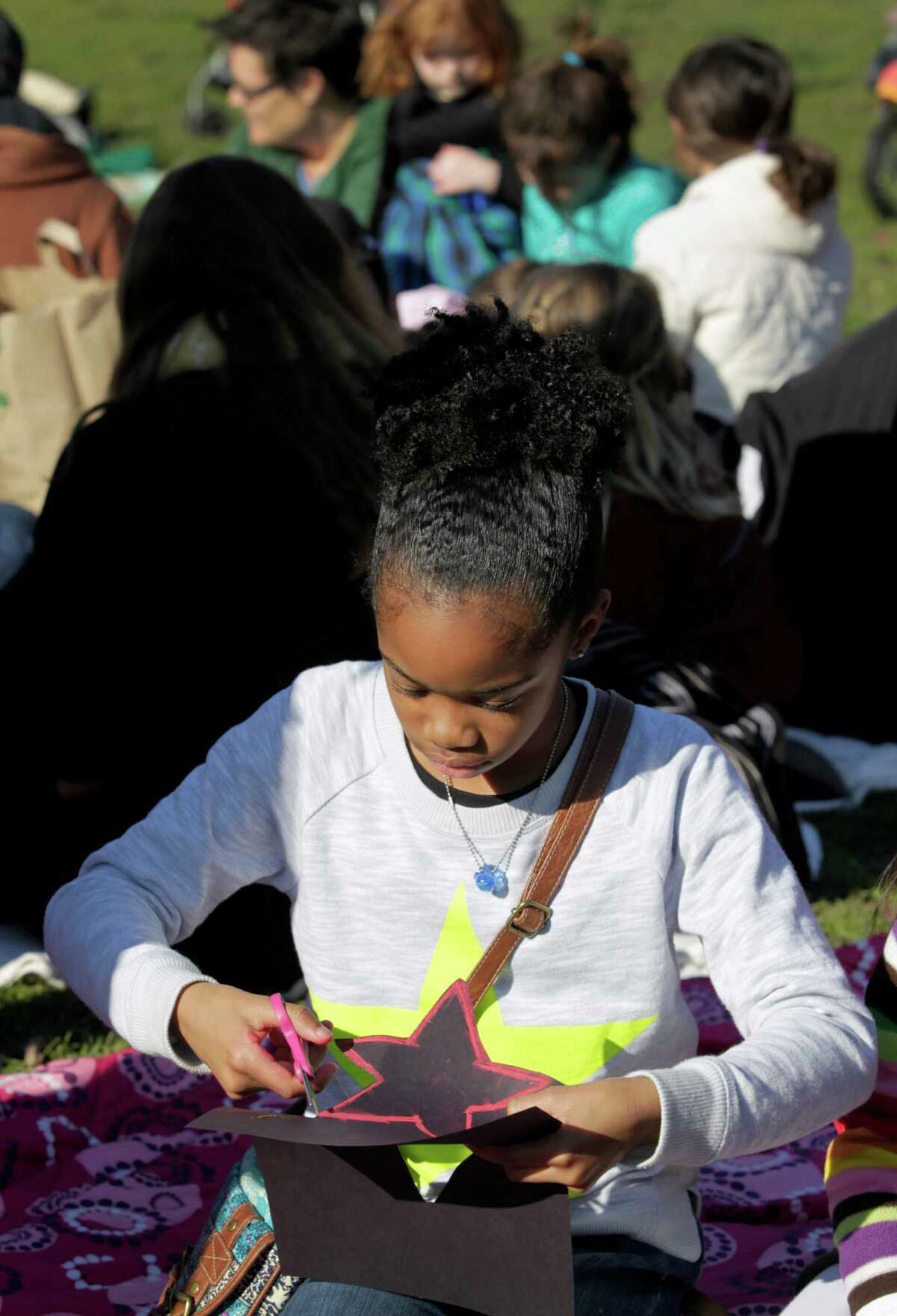De'Yani Dillard, 10, a member of the Radical Brownies youth organization, makes a star at a Black Lives Matter story time action near Lake Merritt in Oakland, Calif. on Saturday, Jan 3, 2015. The Colorful Mamas of the 99 Percent organized the event to engage children in current social and political issues.