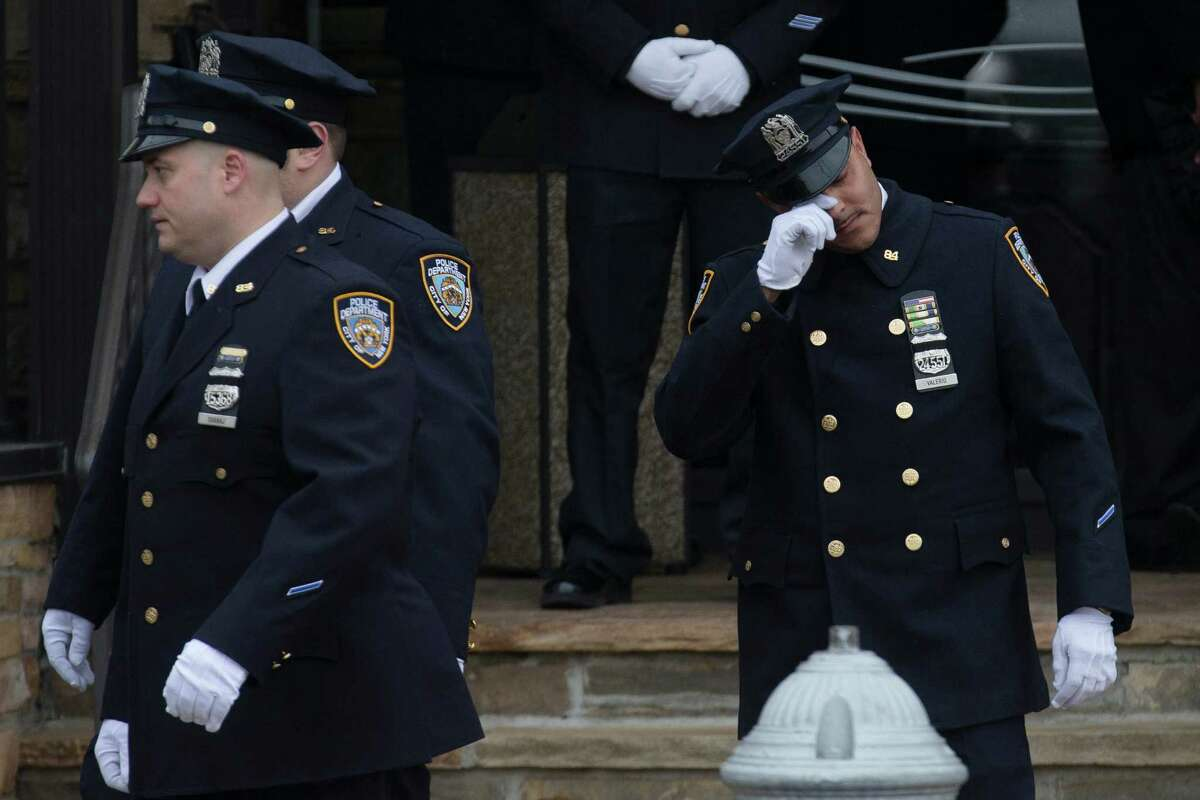 An officer of the 84th Precinct wipes his eyes as he exits the wake of New York Police Department officer Wenjian Liu at Aievoli Funeral Home, Saturday, Jan. 3, 2015, in the Brooklyn borough of New York. Liu and his partner, officer Rafael Ramos, were killed Dec. 20 as they sat in their patrol car on a Brooklyn street. The shooter, Ismaaiyl Brinsley, later killed himself. (AP Photo/John Minchillo)