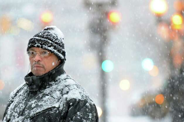 Snow collects on Gus Reyes of Albany as he waits for the bus on North Pearl Street on Saturday, Jan. 3, 2015, in Albany, N.Y. (Cindy Schultz / Times Union) Photo: Cindy Schultz