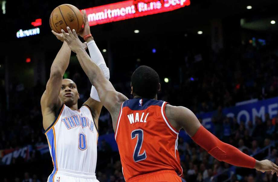 Oklahoma City Thunder guard Russell Westbrook (0) shoots over Washington Wizards guard John Wall (2) during the fourth quarter of an NBA basketball game in Oklahoma City, Friday, Jan. 2, 2015. Oklahoma City won 109-102. (AP Photo/Sue Ogrocki) Photo: Sue Ogrocki / Associated Press / AP