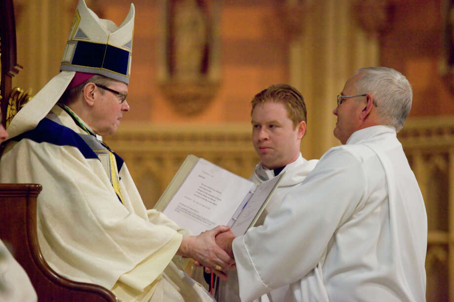 Deaconate candidate Frederick Lesser kneels before Bishop Edward Scharfenberger and promises respect and obedience to him and his successors at Saturday's ceremony in Albany. (Nate Whitchurch) Photo: Photographer: Nathan Whitchurch / Copyright: Whitchurch Photography