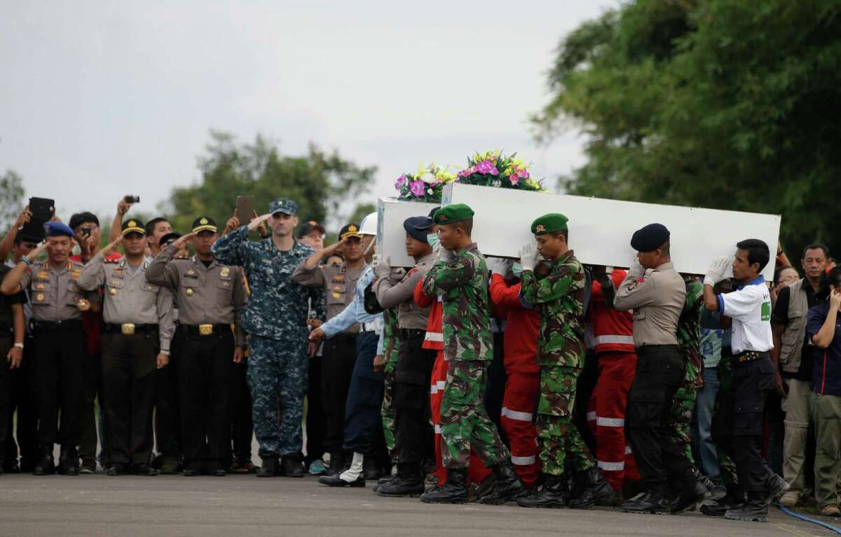 FILE - In this Friday, Jan. 2, 2015 file photo, members of the National Search And Rescue Agency and Indonesian soldier carry coffins bearing bodies of the victims of AirAsia Flight 8501 to transfer them to Surabaya at the airport in Pangkalan Bun, Indonesia. It took nearly two years to find the black boxes from Air France Flight 447, but the Rio de Janeiro to Paris flight that fell into the Atlantic Ocean in the early hours of June 1, 2009, could offer insight into what may have gone wrong on AirAsia's Flight 8501.