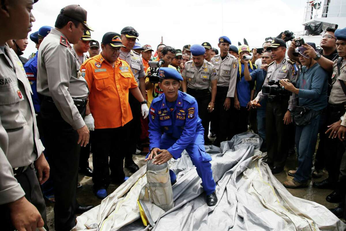 FILE - In this Thursday, Jan. 1, 2015 file photo, Indonesian police carry parts of a plane found floating on the water near the site where AirAsia Flight 8501 disappeared, at Kumai port in Pangkalan Bun, Thursday, Jan. 1, 2015. It took nearly two years to find the black boxes from Air France Flight 447, but the Rio de Janeiro to Paris flight that fell into the Atlantic Ocean in the early hours of June 1, 2009, could offer insight into what may have gone wrong on AirAsia's Flight 8501.