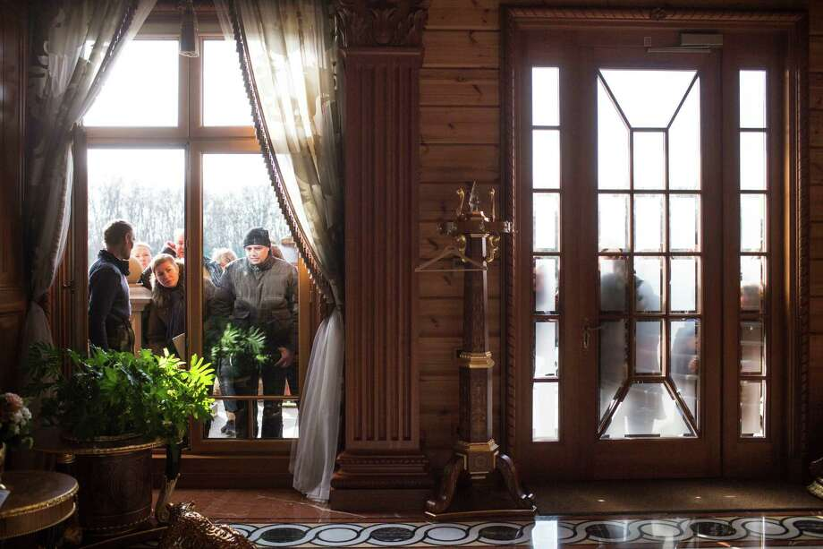 Ukrainians peer into the windows of former President Viktor Yanukovych's lavish estate in Novi Petrivtsi, Ukraine, last Febuary. An investigation by The New York Times found that the president was not so much overthrown as cast adrift by his own allies, particularly those who had borne the brunt of street battles.  Photo: URIEL SINAI, STR / NYTNS
