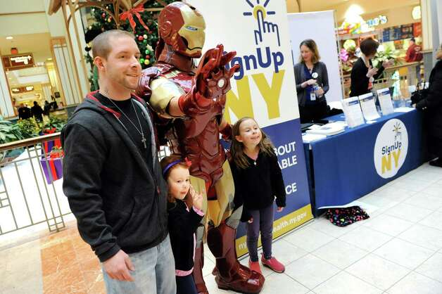 Nathan Laput of Albany, left, and his daughters Mischa Laput, 5, center, and Tatiana Laput, 6, pose with Marvel superhero Iron Man at the Affordable Health Care Insurance booth on Saturday, Jan. 3, 2015, at Colonie Center in Colonie, N.Y. Laput said he was transferring his health insurance from Connecticut to New York. (Cindy Schultz / Times Union) Photo: Cindy Schultz / 00030047A