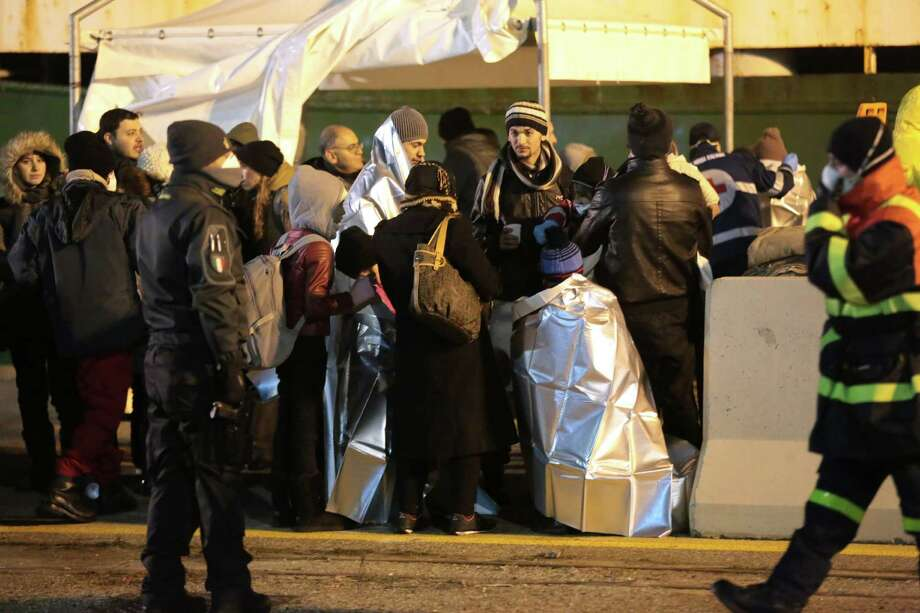 Migrants wait after disembarking from the cargo ship Ezadeen, carrying hundreds of migrants, in the southern Italian port of Corigliano, Italy, Saturday, Jan. 3, 2015. The cargo ship was stopped with about 450 migrants aboard after smugglers sent it speeding toward the coast in rough seas with no one in command. Italian authorities lowered engineers and electricians onto the wave-tossed ship by helicopter to secure it, and the Icelandic Coast Guard towed it to the Italian port of Corigliano late Friday night. Smugglers who bring migrants to Europe by sea appear to have adopted a new, more dangerous tactic: cramming hundreds of them onto a large cargo ship, setting it on an automated course to crash into the coast, and then abandoning the helm. (AP Photo/Antonino D'Urso) Photo: Antonino D'Urso, STR / AP