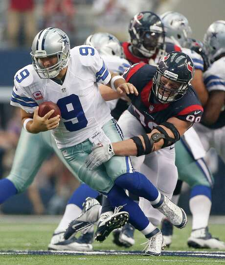 Cowboys quarterback Tony Romo, left, escapes the grasp of Texans defensive end J.J. Watt to throw a touchdown pass in October's battle for Texas supremacy. Dallas has been on a roll ever since. Photo: Karen Warren, Staff / © 2014 Houston Chronicle