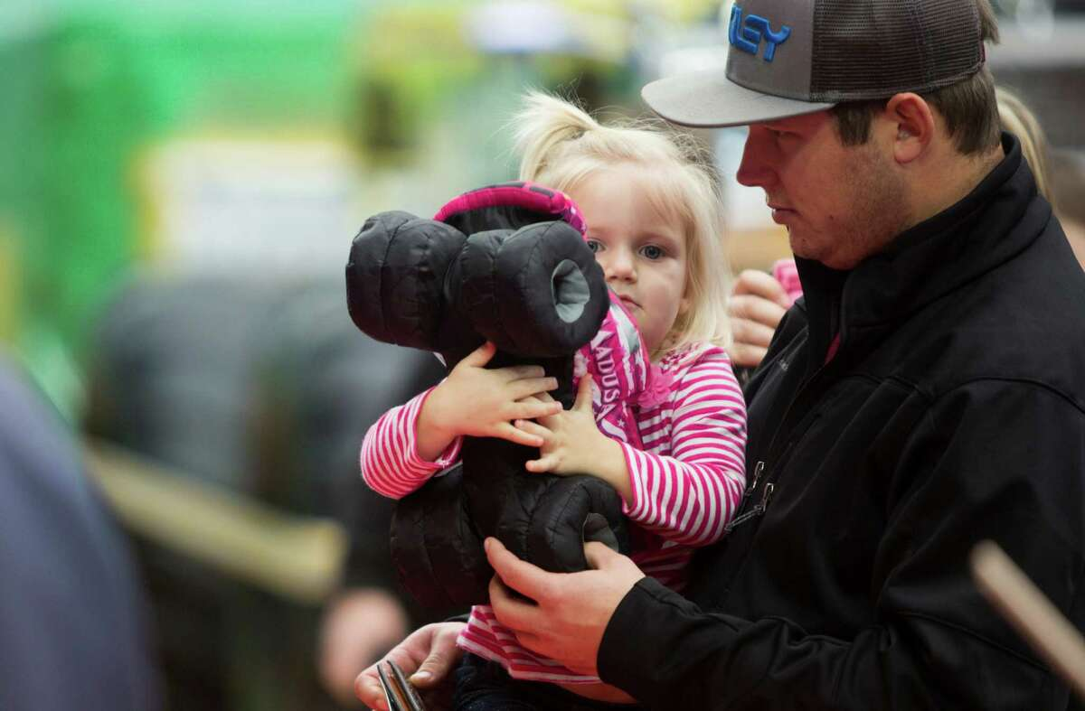 Kensley Stephens, 2, hugs a toy version of the Monster Jam truck Madusa that her father Blaine Stephens, right, got her at the Monster Jam Pit Party, Saturday, Jan. 3, 2015, in Houston.