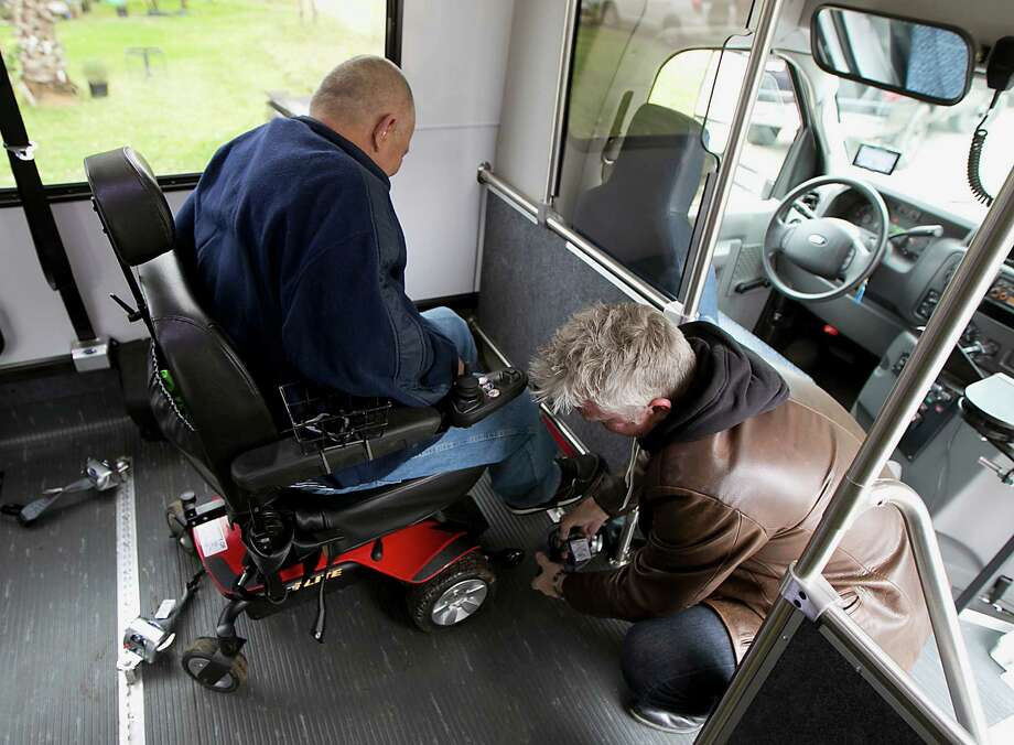 Friendship Center bus service driver Mark Wermund straps in a client who is legally blind and has diabetes in December in Conroe. Photo: James Nielsen, Staff / © 2014  Houston Chronicle