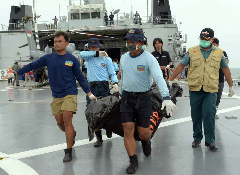 Indonesian's Navy personnel carry a bag containing a dead body of a passenger of AirAsia Flight 8501 at sea off the coast of Pangkalan Bun, Indonesia, Saturday, Jan. 3, 2015. Indonesian officials were hopeful Saturday they were honing in on the wreckage of AirAsia Flight 8501 after sonar equipment detected two large objects on the ocean floor, a full week after the plane went down in stormy weather. (AP Photo/Adek Berry, Pool) ORG XMIT: XTS117 Photo: Adek Berry / AFP POOL
