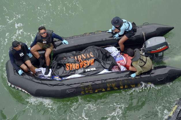 Indonesian Navy personnel carry a plastic bag containing the dead body of a passenger of AirAsia Flight 8501 at sea off the coast of Pangkalan Bun, Indonesia, Saturday, Jan. 3, 2015. Indonesian officials were hopeful Saturday they were honing in on the wreckage of the flight after sonar equipment detected two large objects on the ocean floor, a full week after the plane went down in stormy weather. (AP Photo/Adek Berry, Pool) ORG XMIT: XTS121 Photo: Adek Berry / POOL AFP