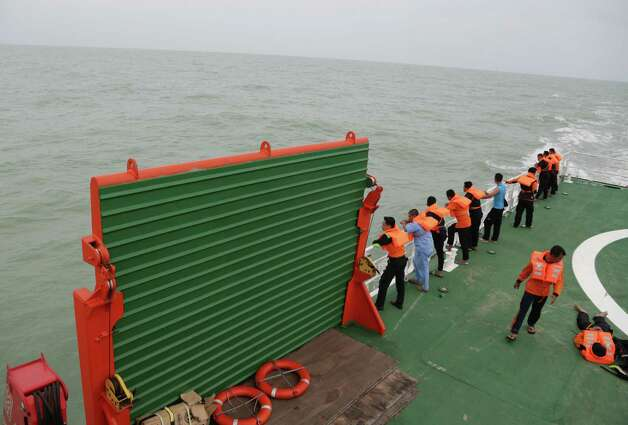 Members of the National Search And Rescue Agency (BASARNAS) stand on KN SAR Purworejo ship during a search operation for the victims of AirAsia flight QZ 8501 on the Java Sea, Indonesia, Saturday, Jan. 3, 2015. Indonesian officials were hopeful Saturday they were honing in on the wreckage of the ill-fated jetliner after sonar equipment detected large objects on the ocean floor, one week after the plane went down in stormy weather. (AP Photo/Achmad Ibrahim) ORG XMIT: AI103 Photo: Achmad Ibrahim / AP