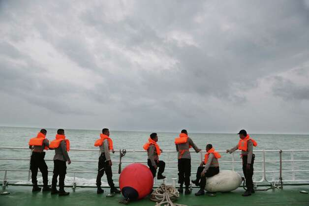 Indonesian police stand on the deck of a National Search And Rescue Agency (BASARNAS) ship during a search operation for the victims of AirAsia flight QZ 8501 on the Java Sea, Indonesia, Saturday, Jan. 3, 2015. Indonesian officials were hopeful Saturday they were honing in on the wreckage of the ill-fated jetliner after sonar equipment detected large objects on the ocean floor, one week after the plane went down in stormy weather. (AP Photo/Achmad Ibrahim) ORG XMIT: AI102 Photo: Achmad Ibrahim / AP