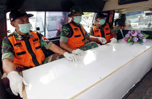 Indonesian military personnel sit with a coffin containing the body of a victim of AirAsia Flight 8501 in an ambulance upon arrival at Juanda Naval Airbase in Surabaya, East Java, Indonesia, Saturday, Jan. 3, 2015. Indonesian officials were hopeful Saturday they were honing in on the wreckage of the flight after sonar equipment detected two large objects on the ocean floor, a full week after the plane went down in stormy weather. (AP Photo/Trisnadi) ORG XMIT: XFL106 Photo: Trisnadi / AP