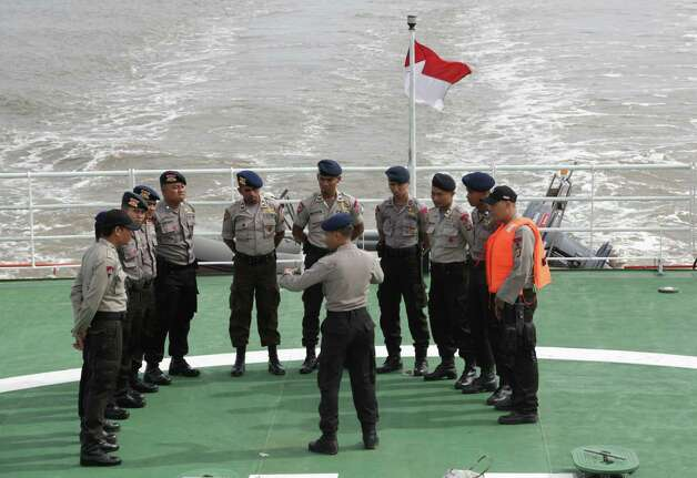Indonesian police stand on the deck of the National Search And Rescue Agency (BASARNAS) ship during a search operation for the victims of AirAsia flight QZ 8501 at Java Sea, Indonesia, Saturday, Jan. 3, 2015. Indonesian officials were hopeful Saturday they were honing in on the wreckage of the ill-fated jetliner after sonar equipment detected large objects on the ocean floor, one week after the plane went down in stormy weather. (AP Photo/Achmad Ibrahim) ORG XMIT: AI101 Photo: Achmad Ibrahim / AP