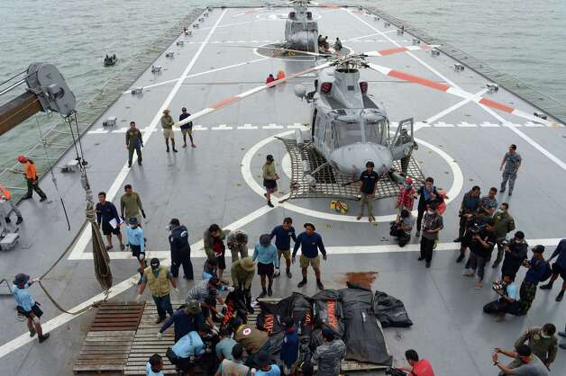 Indonesian's Navy personnel prepare the dead bodies of the passengers of AirAsia Flight 8501, on Indonesian navy vessel KRI Banda Aceh, to transfer them by helicopters at sea off the coast of Pangkalan Bun, Indonesia, Saturday, Jan. 3, 2015. Indonesian officials were hopeful Saturday they were honing in on the wreckage of AirAsia Flight 8501 after sonar equipment detected two large objects on the ocean floor, a full week after the plane went down in stormy weather. (AP Photo/Adek Berry,Pool) ORG XMIT: XTS113 Photo: Adek Berry / AFP POOL