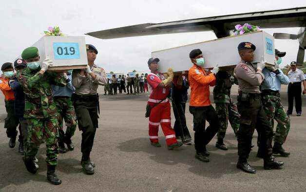 Members of the National Search and Rescue Agency carry coffins containing bodies of the victims aboard AirAsia Flight 8501 to transfer to Surabaya at the airport in Pangkalan Bun, Indonesia, Saturday, Jan. 3, 2015. Indonesian officials were hopeful Saturday they were honing in on the wreckage of the flight after sonar equipment detected two large objects on the ocean floor, a full week after the plane went down in stormy weather. (AP Photo/Tatan Syuflana) ORG XMIT: XTS108 Photo: Tatan Syuflana / AP