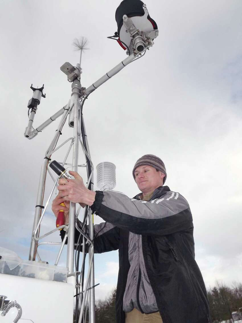 Dmitry Kalyadin, a systems engineer for YSI Integrated Systems and Services, installs a weather sensor station near Lake George Thursday morning, Dec. 18, 2014, in Ticonderoga, N.Y. (Brian Nearing/Times Union)