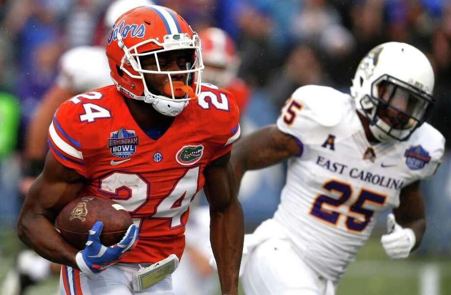 Florida defensive back Brian Poole (24) returns an interception for a touchdown during the first half of an Birmingham Bowl NCAA college football game against East Carolina Saturday, Jan. 3, 2015, in Birmingham, Ala. (AP Photo/Butch Dill) ORG XMIT: ALBD108 Photo: Butch Dill / FR111446 AP