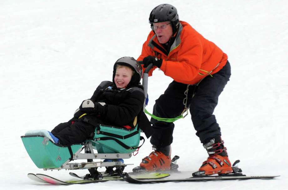 Volunteer Dave Roberts of Corinth does a fun run down the slope with 9-year-old Shamus Evans of Galway during a day on the slopes and visit from Olympian Andrew Weibrecht at the Double H Hole in the Woods Ranch on Saturday Jan. 3, 2015 in Lake Luzerne, N.Y. (Michael P. Farrell/Times Union) Photo: Michael P. Farrell / 00030020A