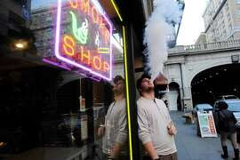 Manager Sean Trataris smokes an e-cigarette at Vapor Smoke Shop in San Francisco.