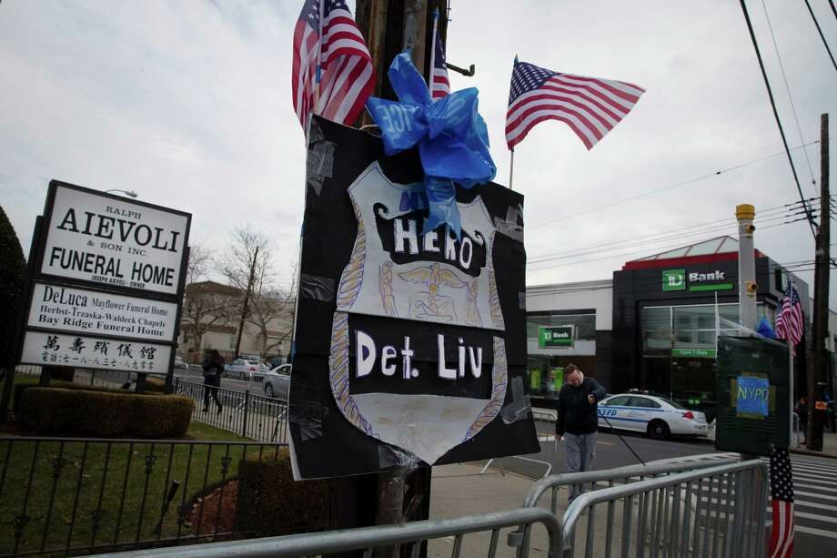 A sign praising the New York Police Department hangs outside Aievoli Funeral Home before the wake of NYPD Officer Wenjian Liu, Saturday, Jan. 3, 2015, in the Brooklyn borough of New York. Liu and his partner, Officer Rafael Ramos, were killed Dec. 20, as they sat in their patrol car on a Brooklyn street. The shooter, Ismaaiyl Brinsley, later killed himself. (AP Photo/John Minchillo) Photo: John Minchillo, FRE / FR170537 AP