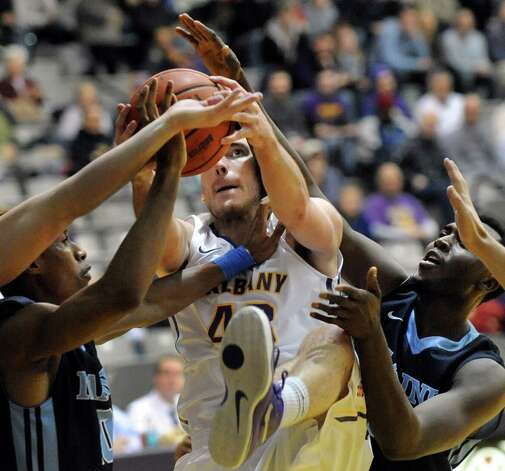 UAlbany's Greig Stire, center, fights for a rebound during their basketball game against Maine on Saturday, Jan. 3, 2015, at SEFCU Arena in Albany, N.Y. (Cindy Schultz / Times Union) Photo: Cindy Schultz / 00029991A