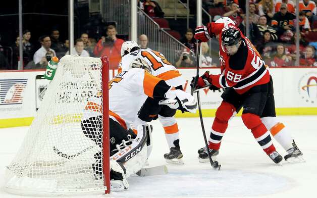 New Jersey Devils right wing Jaromir Jagr (68), of the Czech Republic, scores a goal against Philadelphia Flyers goalie Steve Mason, left, during the second period of an NHL hockey game, Saturday, Jan. 3, 2015, in Newark, N.J. (AP Photo/Julio Cortez) ORG XMIT: NJJC107 Photo: Julio Cortez / AP