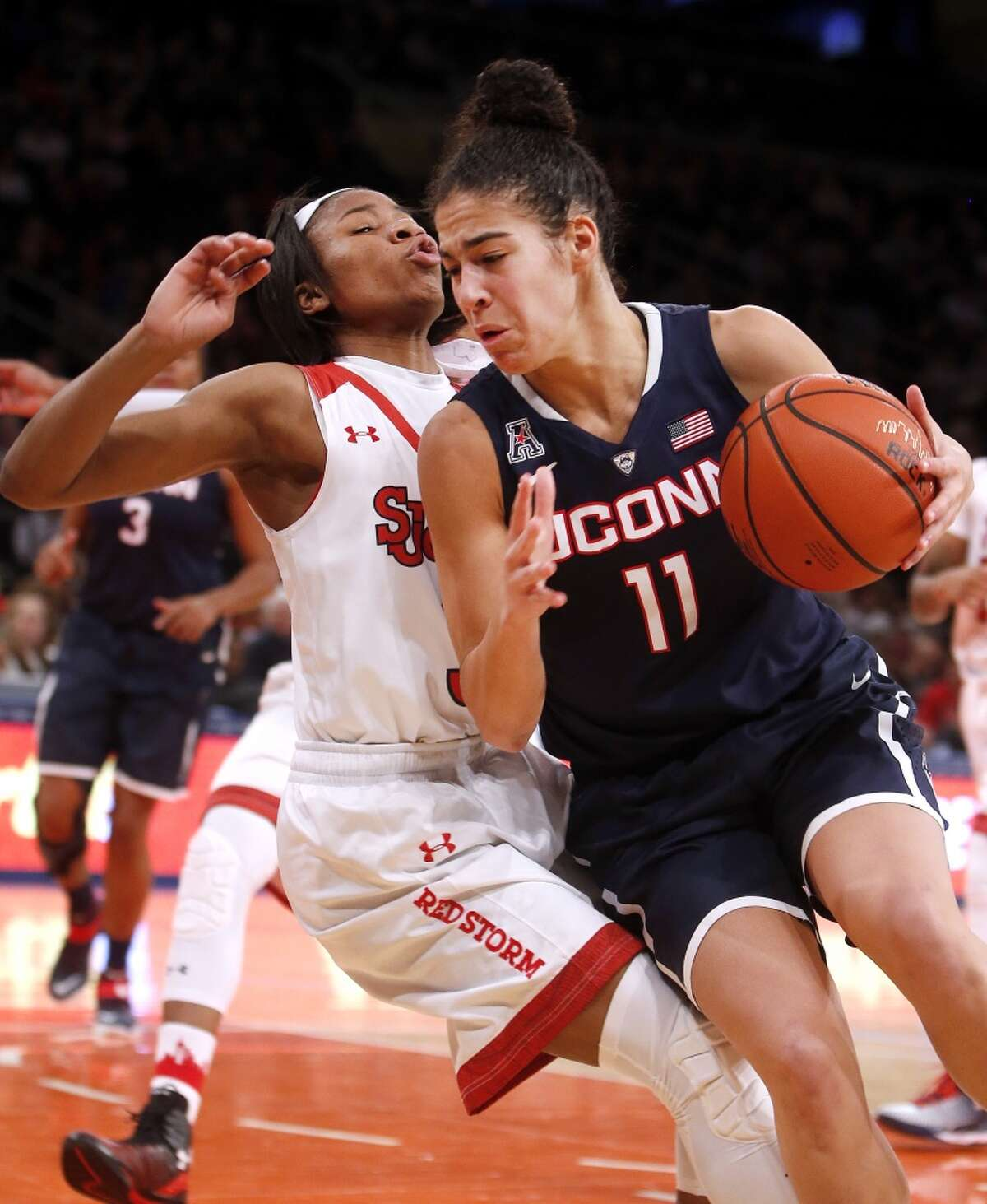 Connecticut's Kia Nurse (11) is fouled as she drives against St. John's Aliyyah Handford during the second half of an NCAA college basketball game, Sunday, Jan. 4, 2015, in New York. Connecticut defeated St. John's 70-54. (AP Photo/Jason DeCrow)