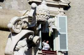 Pope Francis greets the faithful in St. Peter's Square from the window of the papal library.