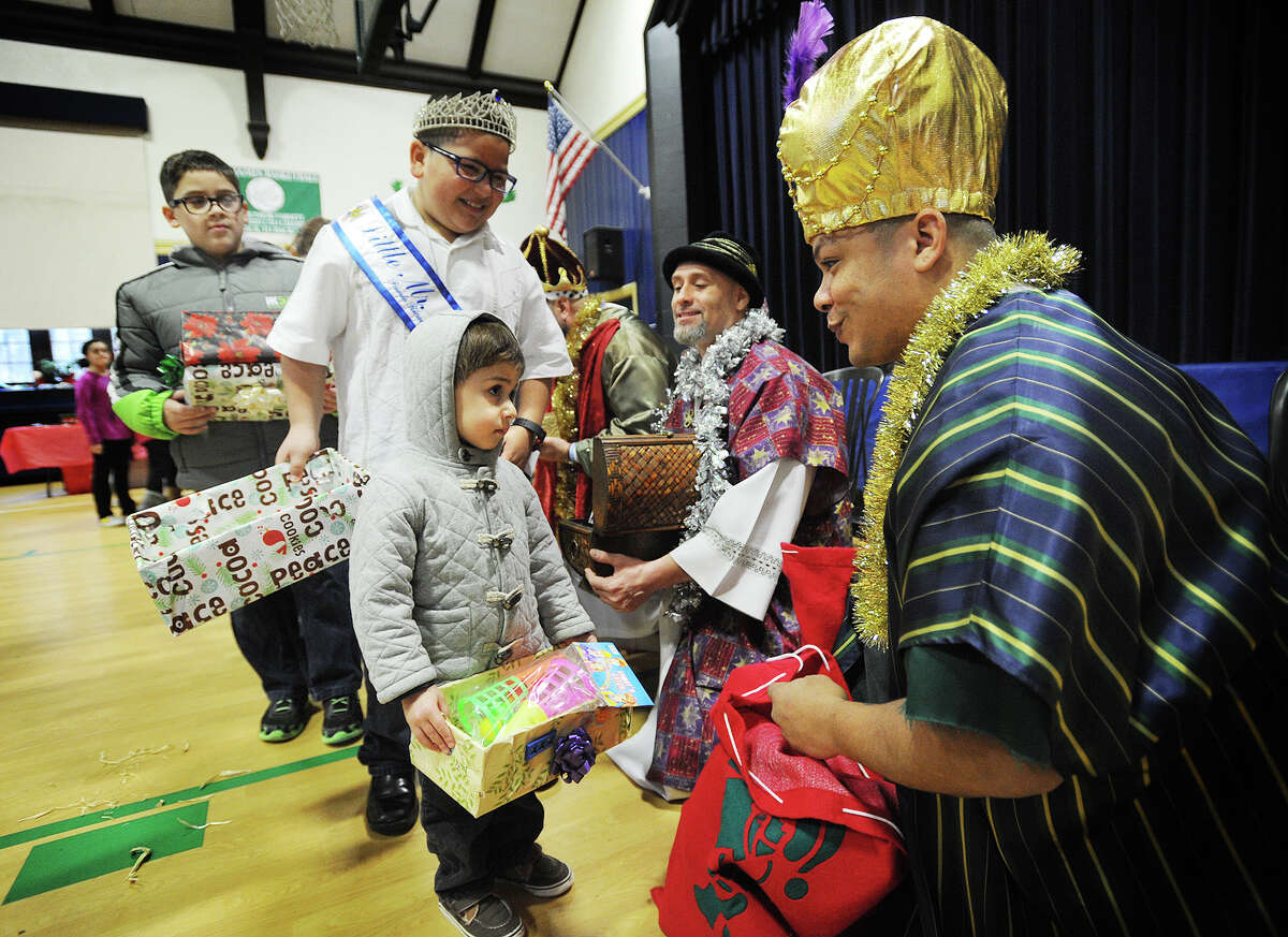 Nicholas Karamanian, 3, of Stratford, receives a present from one of the Three Kings, Jose Lopez, of Bridgeport, at the Stratford Hispanic Heritage Committe's annual Three Kings Day celebration at the St. James School gymnasium in Stratford, Conn. on Sunday, January 4, 2014. Celebrating the visit of the Three Kings to the baby Jesus, children place decorated boxes beneath their beds, into which gifts are left for them.