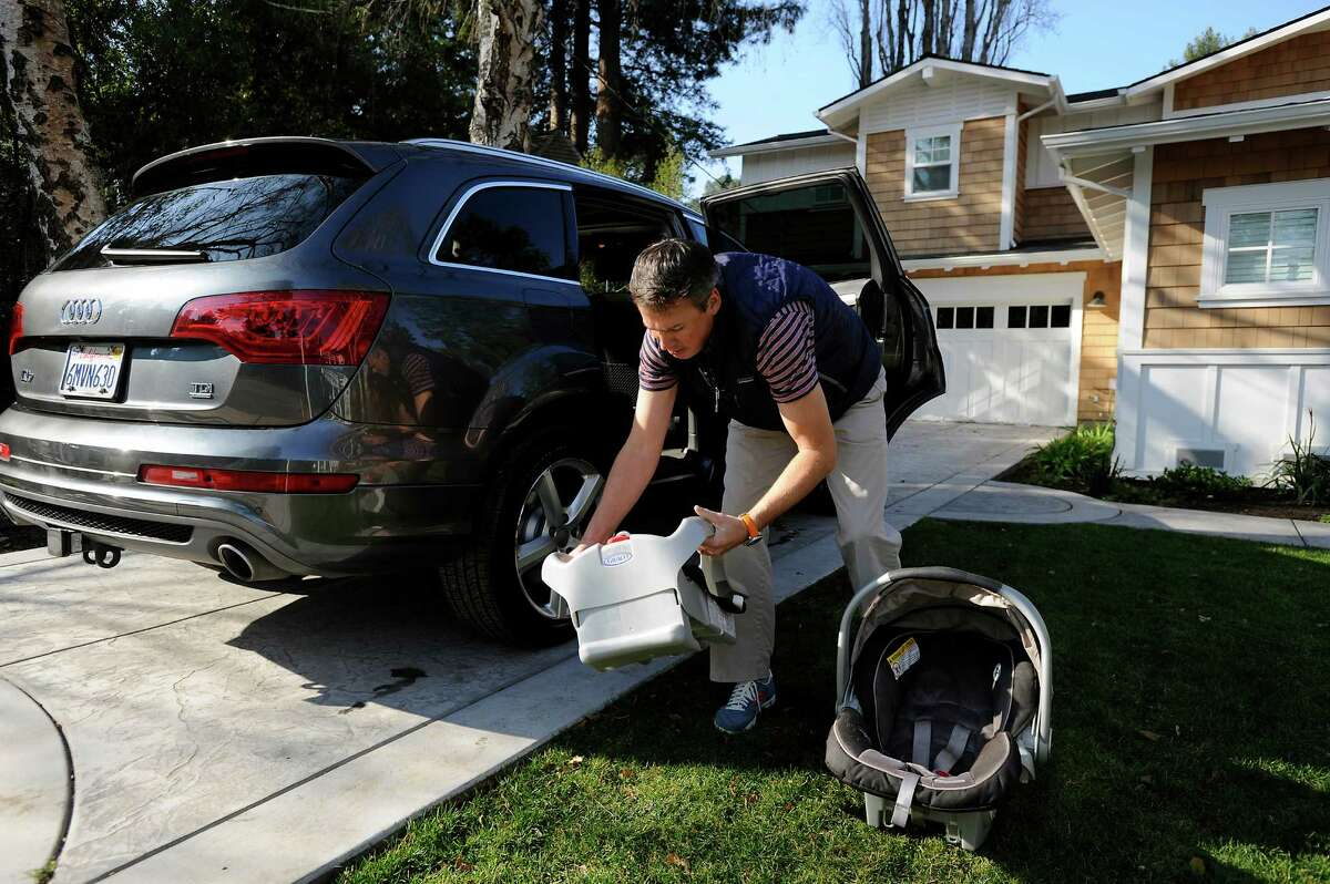 Bryan Crawley, owner of Buckled Baby, a company that teaches parents in the Bay Area how to properly install and buckle their children into car seats, installs the base for a rear facing carseat into his car at his home in Mill Valley, CA, on Friday, January 2, 2015.