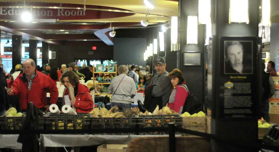 Shoppers look over the produce and other food items for sale at the Schenectady Greenmarket on Sunday, Jan. 4, 2015, in Schenectady, N.Y. During the winter months the market is held on Sundays inside Proctors.  (Paul Buckowski / Times Union) Photo: Paul Buckowski / 00030067A