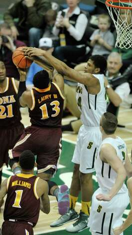 David Laury  of Iona, left, has his shot blocked by Lavon Long of Siena during their game at the Times Union Center on Sunday, Jan. 4, 2014, in Albany, N.Y.   (Paul Buckowski / Times Union) Photo: Paul Buckowski / 00030029A