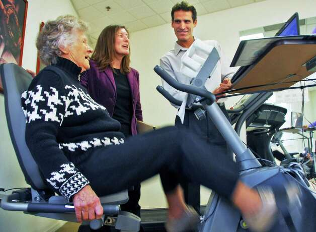 File photo -- Prestwick Chase Senior Housing resident Marion Buchanan, 98, left, pedals the cybercycle under the direction of Union College assistant professor Cay Anderson-Hawley and Skidmore College associate professor Paul Arciero, right, in a virtual bike race, part of a research project with Union and Skidmore Colleges in the Prestwick Chase excercise room Friday afternoon Nov. 21, 2008,  in Saratoga Springs, N.Y. (John Carl D'Annibale/Times Union) Photo: John Carl D'Annibale / 00001316A