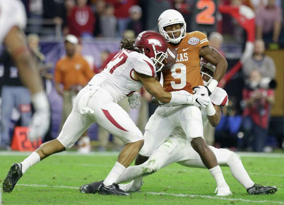 Texas' John Harris can't get away from the Arkansas defense during a Texas Bowl that included only 59 yards of offense by the Longhorns. Photo: Brett Coomer, Houston Chronicle / © 2014 Houston Chronicle
