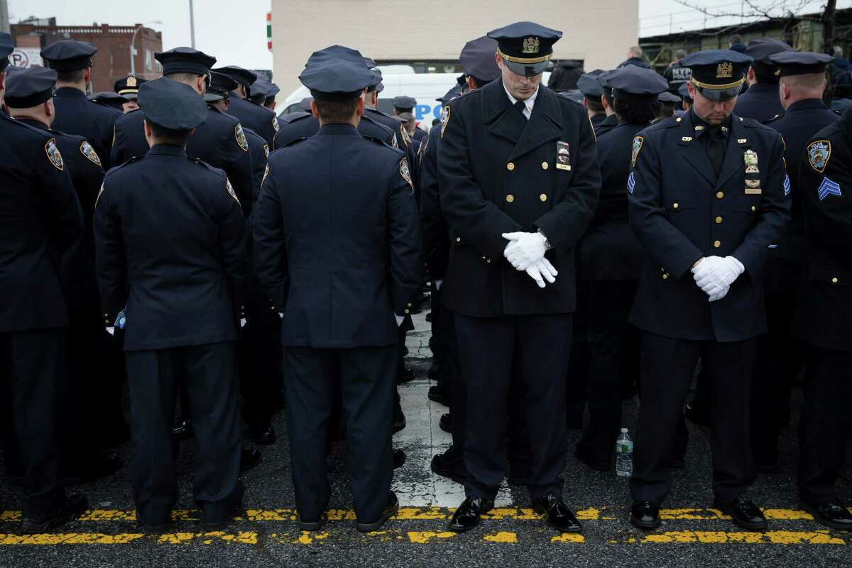 Some police officers, left, turn their backs in a sign of disrespect as Mayor Bill de Blasio speaks as others, at right front line, stand at attention, during the funeral of New York Police Department Officer Wenjian Liu at Aievoli Funeral Home, Sunday, Jan. 4, 2015, in the Brooklyn borough of New York. Liu and his partner, officer Rafael Ramos, were killed Dec. 20 as they sat in their patrol car on a Brooklyn street. The shooter, Ismaaiyl Brinsley, later killed himself.
