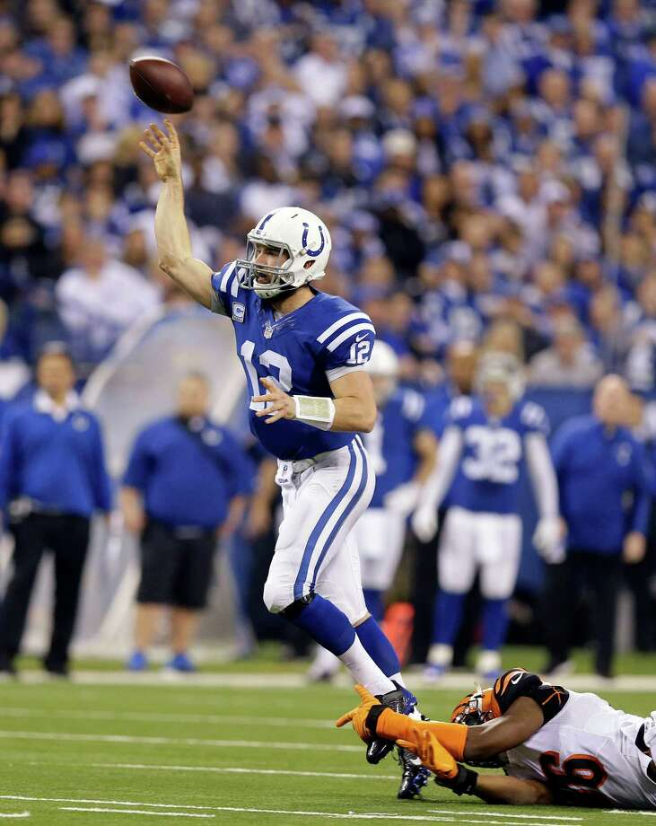 Indianapolis Colts quarterback Andrew Luck (12) throws a 36-yard touchdown pass as he is tackled by Cincinnati Bengals' Carlos Dunlap (96) during the second half of an NFL wildcard playoff football game Sunday, Jan. 4, 2015, in Indianapolis. (AP Photo/Michael Conroy) ORG XMIT: NAS129 Photo: Michael Conroy / AP
