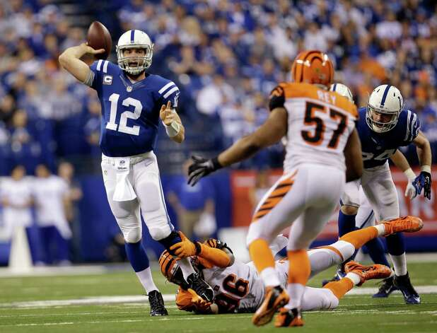 Indianapolis Colts quarterback Andrew Luck (12) throws a 36-yard touchdown pass as he is tackled by Cincinnati Bengals' Carlos Dunlap (96) during the second half of an NFL wildcard playoff football game Sunday, Jan. 4, 2015, in Indianapolis. (AP Photo/AJ Mast) ORG XMIT: NAS128 Photo: AJ Mast / FR123854 AP