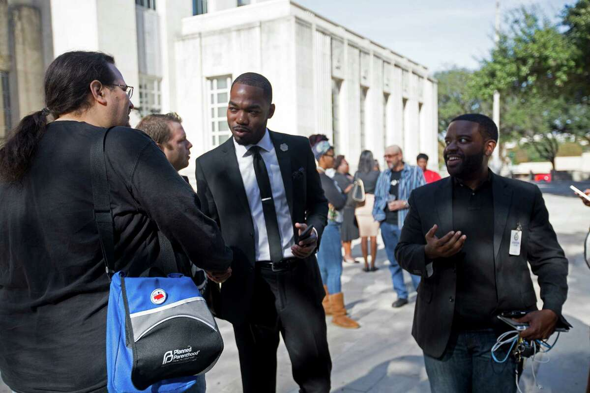 Damien Thaddeus Jones, 29, center, and Durrel Douglas, 28, right talk to a Houston supporter outside of City Hall on Tuesday, Dec. 9.